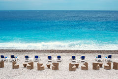 Chairs and tables on Nice beach along Promenade des Anglais Stock Photo