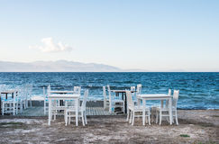 Chairs and tables in old cafe near the sea Royalty Free Stock Photos