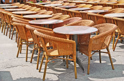 Chairs and tables in row. Restaurant street terrace with wicker chairs and round tables Stock Photography
