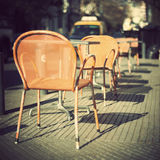 Chairs and tables in the sidewalk Stock Photos