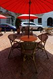 Chairs and tables of a street cafe 2. Chairs and tables of a street cafe made of wood, metal and rattan, with the red sunshade royalty free stock image