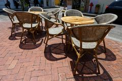Chairs and tables of a street cafe 5. Chairs and tables of a street cafe made of wood, metal and rattan, with the red sunshade stock photo