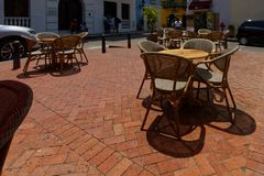Chairs and tables of a street cafe 4. Chairs and tables of a street cafe made of wood, metal and rattan, with the red sunshade royalty free stock photos