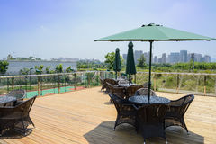 Chairs,tables and sunshades on planked roof terrace of uptown bu Stock Photos