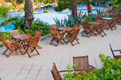 Chairs, tables and  swimming pool early morning. Stock Photos