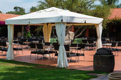 Chairs and Tables under Gazebo with White Tent Stock Photo