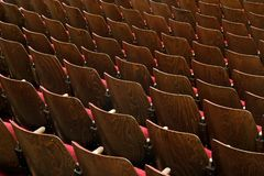 Chairs in theater. Wooden chairs with red fabric, no numbers, theatre scene Royalty Free Stock Images