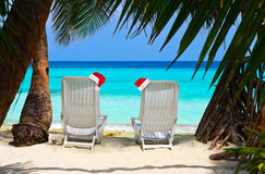 Chairs on tropical beach and Santa Claus red christmas hat Stock Photos