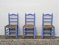 Chairs in a typical Andalusian street. Three wooden chairs in a typical Andalusian street Royalty Free Stock Photography