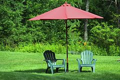 Chairs and umbrella. Adirondack chairs on grass with red umbrella Stock Images