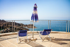 Chairs and umbrella on balcony overlooking ocean and rocks Stock Photo