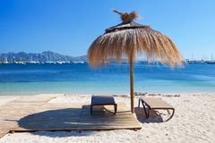 Chairs and umbrella on the beach. In Port de Pollenca, Majorca, Spain royalty free stock images