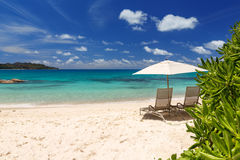 Chairs and umbrella on a beautiful tropical beach of Seychelles Stock Photo