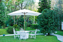 Chairs with umbrella in the garden Stock Photo