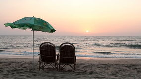 Chairs and umbrella near coastline at sunset time stock video footage