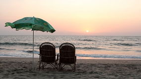 Chairs and umbrella near coastline at sunset time. Two chairs and umbrella near coastline at sunset time stock footage