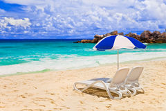 Chairs and umbrella at tropical beach. Vacations background Stock Images