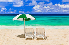 Chairs and umbrella at tropical beach. Vacations background Royalty Free Stock Image