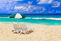 Chairs and umbrella at tropical beach. Vacations background Royalty Free Stock Images