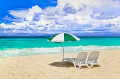 Chairs and umbrella at tropical beach. Vacations background Stock Photos