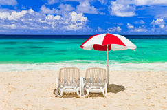 Chairs and umbrella at tropical beach. Vacations background Stock Photography