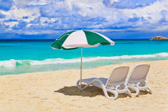 Chairs and umbrella at tropical beach. Vacations background Royalty Free Stock Photos