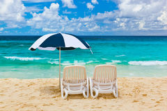 Chairs and umbrella at tropical beach. Vacations background Royalty Free Stock Photo