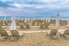 Chairs and umbrellas on a beautiful beach at Sunny Beach on the Black Sea coast of Bulgaria. Lounge blue bulgarian clouds coastline day horizontal morning no stock photo
