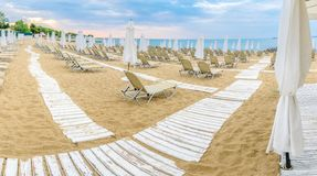 Chairs and umbrellas on a beautiful beach at Sunny Beach on the Black Sea coast of Bulgaria. Lounge blue bulgarian clouds coastline day horizontal leisure stock photo