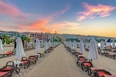 Chairs and umbrellas on a beautiful beach at sunrise in Sunny Beach on the Black Sea coast of Bulgaria. Lounge blue bulgarian clouds coastline dawn day stock photography