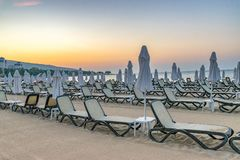 Chairs and umbrellas on a beautiful beach at sunrise in Sunny Beach on the Black Sea coast of Bulgaria. Lounge bulgarian coastline dawn day horizontal morning stock images