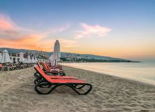 Chairs and umbrellas on a beautiful beach at sunrise in Sunny Beach on the Black Sea coast of Bulgaria. Lounge blue bulgarian clouds coastline dawn day royalty free stock photography