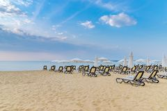 Chairs and umbrellas on a beautiful beach at sunrise in Sunny Beach on the Black Sea coast of Bulgaria. Lounge blue bulgarian clouds coastline copy space royalty free stock image