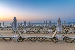 Chairs and umbrellas on a beautiful beach at sunrise in Sunny Beach on the Black Sea coast of Bulgaria. Lounge bulgarian coastline copy space copyspace dawn day royalty free stock photo