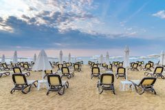 Chairs and umbrellas on a beautiful beach at sunrise in Sunny Beach on the Black Sea coast of Bulgaria. Lounge blue bulgarian clouds coastline day horizontal royalty free stock photo