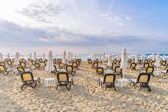 Chairs and umbrellas on a beautiful beach at sunrise in Sunny Beach on the Black Sea coast of Bulgaria. Lounge blue bulgarian clouds coastline day horizontal royalty free stock photography