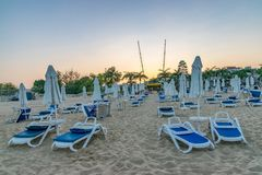 Chairs and umbrellas on a beautiful beach at sunset in Sunny Beach on the Black Sea coast of Bulgaria. Lounge bulgarian coastline dawn day horizontal no people royalty free stock photo