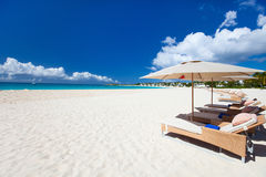 Chairs and umbrellas on tropical beach Royalty Free Stock Photos