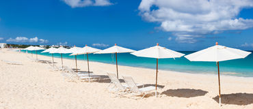 Chairs and umbrellas on tropical beach. Row of chairs and umbrellas on a beautiful tropical beach at Anguilla, Caribbean Stock Photo