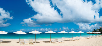 Chairs and umbrellas on tropical beach. Row of chairs and umbrellas on a beautiful tropical beach at Anguilla, Caribbean Royalty Free Stock Images