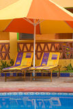 Chairs Under A Poolside Umbrella. Brightly colored lounge chairs sit under a yellow and orange umbrella at the edge of a pool in tropical Mexico Royalty Free Stock Photo