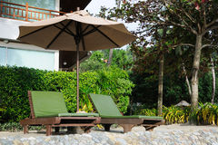 Chairs under the umbrella. Two green chairs in the garden resort Royalty Free Stock Photos