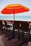 Chairs under an umbrella on a pier Royalty Free Stock Photography