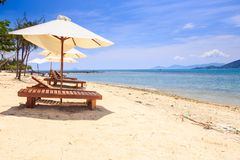 Chairs under White Umbrellas on Sand Beach by Sea Royalty Free Stock Images