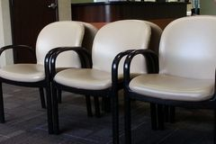 Chairs in waiting room. Six chairs in waiting room, off-white vinyl with black metal frames Royalty Free Stock Photo