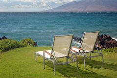 Chairs and water. Lounge chairs overlooking the water Stock Image