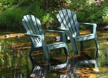 Chairs in water. Adirondack chairs in the brook Stock Image