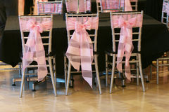 Chairs for wedding. Three chairs in a row with a big pink bow tied behind them for an event Royalty Free Stock Photo