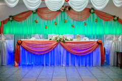 Chairs in white covers with a white ribbon. Wedding table with blue and green light Stock Photography