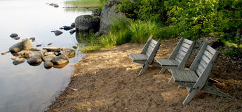 Chairs on wild beach on a lake Stock Images